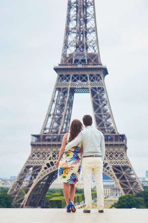 Romantic loving couple having a date near the Eiffel tower. Tourists on vacation or during their honeymoon in Paris, France