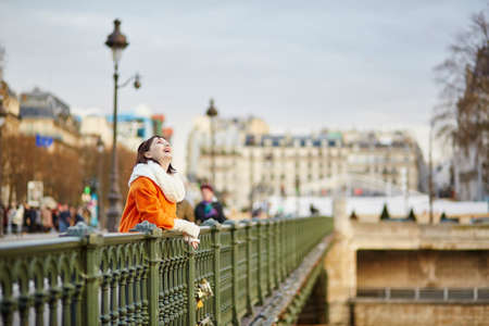 Cheerful young woman in orange coat walking on a street of Paris decorated for Christmas photo