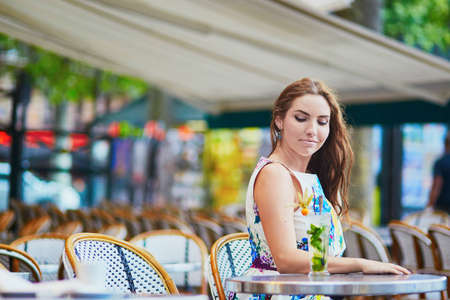 french woman: Smiling French woman sitting on the open terrace of Parisian cafe with cocktail on a summer day Stock Photo