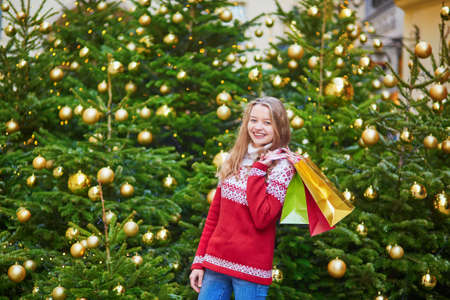 Cheerful young woman on a street of Paris decorated for Christmas with shopping bags