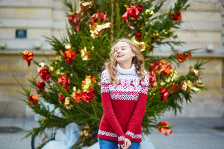 Girl with a brightly decorated Christmas tree in Paris