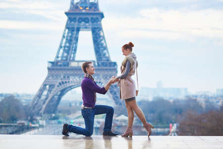 Romantic engagement in Paris, man proposing to his beautiful girlfriend near the Eiffel tower Stock Photo