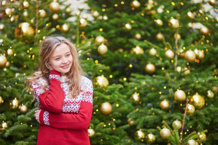 Cheerful young woman on a street of Paris decorated for Christmas Stock Photo