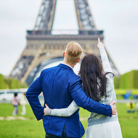 Happy couple looking at the Eiffel tower. Tourists enjoying their vacation in France. Romantic date or traveling couple concept Stock Photo