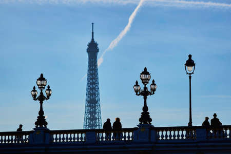 alexandre: Scenic cityscape of Paris with silhouettes of people and lanterns on the famous Alexandre III bridge and the Eiffel tower over the blue sky