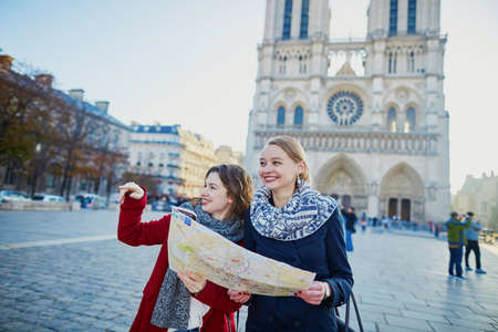 2 way: Two young girls walking together in Paris with map near Notre-Dame cathedral. Tourism or friendship concept Stock Photo