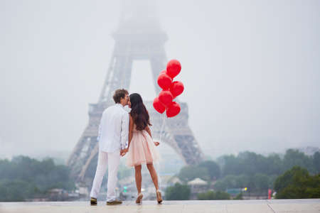 구름과 안개 비오는 날에 파리에서 함께 에펠 탑 근처의 빨간 풍선의 무리와 함께 사랑의 아름 다운 로맨틱 커플