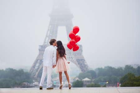 Mooi romantisch paar in liefde met bos van rode ballons samen dichtbij de toren van Eiffel in Parijs op een bewolkte en mistige regenachtige dag