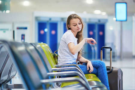 Beautiful young tourist girl with backpack and carry on luggage in international airport, waiting for her flight, looking worried. Delayed or canceled flight concept