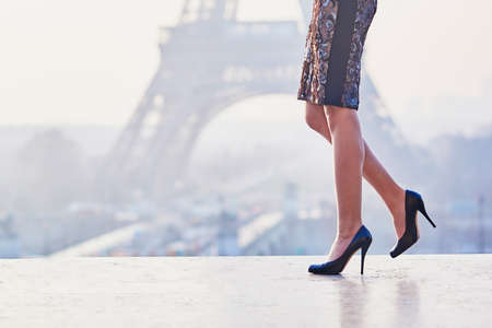Woman wearing high heels shoes and walking near the Eiffel tower at early morning in Paris, closeup of legs Stock Photo
