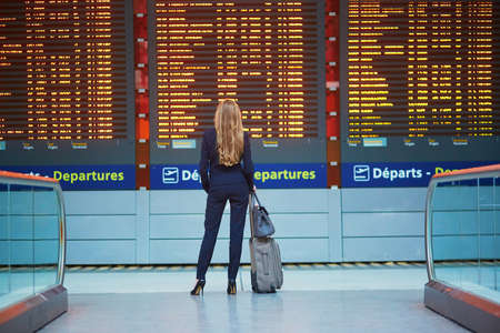 Young elegant business woman with hand luggage in international airport terminal, looking at information board, checking her flight. Cabin crew member with suitcase. Banque d'images