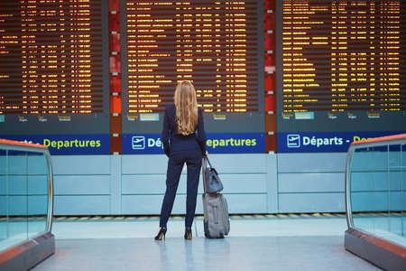 Jonge elegante zakenvrouw met handbagage in de internationale terminal van de luchthaven, op zoek naar informatie board, haar vlucht controleren. Lid van het cabinepersoneel met koffer.