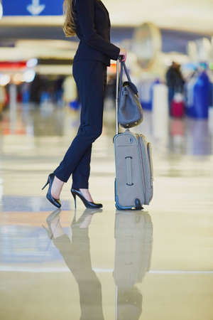 Elegant business woman with hand luggage in international airport terminal. Cabin crew member with suitcase. Unrecognizable person, closeup of legs Stock Photo