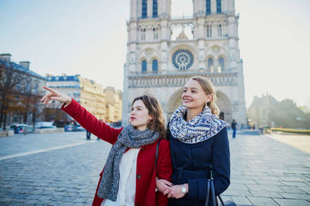 Two young girls walking together in Paris near Notre-Dame cathedral. Tourism or friendship concept
