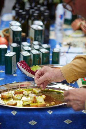 degustating: Man degustating bread with fresh extra virgin olive oil on farmer market in Tuscany, Italy