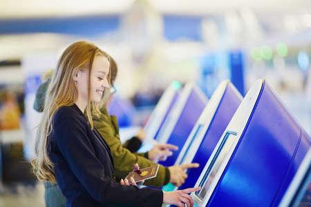 여권 및 탑승권을 들고 국제 공항 터미널에서자가 체크인하는 젊은 우아한 비즈니스 여인