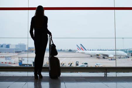 飛行機の窓から見る国際空港で手荷物を持つ若いエレガントなビジネス女性のシルエット。スーツケースを持つキャビン クルー メンバー。旅行の概 写真素材