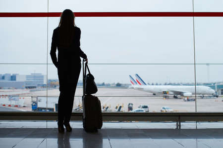 Silhouette of a young elegant business woman with hand luggage in international airport, looking through the window at planes. Cabin crew member with suitcase. Travel concept