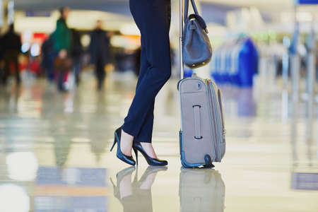 unrecognizable person: Elegant business woman with hand luggage in international airport terminal. Cabin crew member with suitcase. Unrecognizable person, closeup of legs Stock Photo