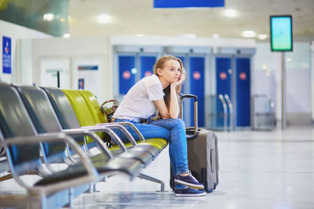 Beautiful young tourist girl with backpack and carry on luggage in international airport, waiting for her flight, looking upset. Delayed or canceled flight concept