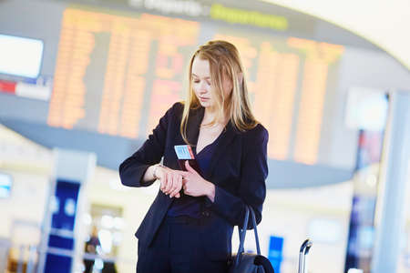 Young elegant business woman holding passport and boarding pass, checking time near flight information board in international airport terminal Stock Photo