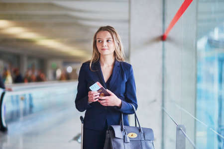 Young elegant business woman with hand luggage looking through the window in international airport terminal, waiting for her flight
