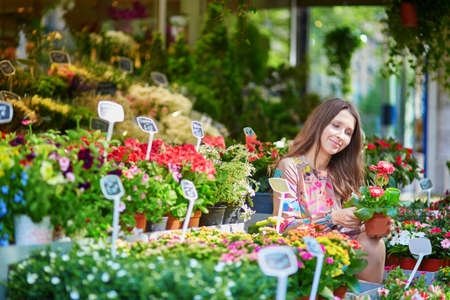 Beautiful young woman selecting flowers on Parisian flower market or in shop on a summer day