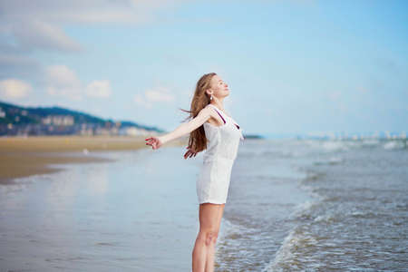 normandy: Beautiful young woman enjoying her vacation by ocean or sea, walking in water. People on sea vacation concept