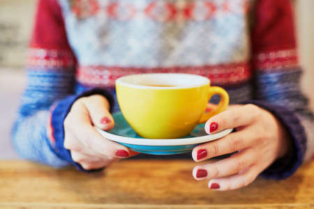 Beautiful woman hands with red manicure and cup of fresh hot coffee on wooden table. Selective focus