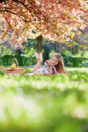 Beautiful young woman having picnic on sunny spring day in park during cherry blossom season, eating sweets and fruits