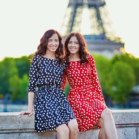 Beautiful twin sisters in red and black polka dot dresses in front of the Eiffel tower in Paris, France