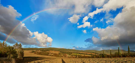 Scenic panorama of Tuscany countryside with full rainbow over the blue sky at rainy weather Stock Photo