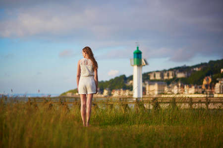 normandy: Beautiful young woman at sunset on meadow near lighthouse in Deaville, Normandy, Northern France, Europe Stock Photo