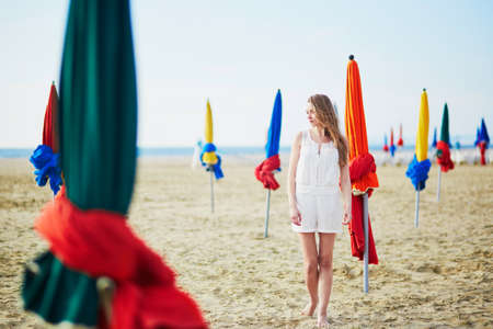 normandy: Beautiful young woman with famous colorful parasols on Deauville Beach, Normandy, Northern France, Europe