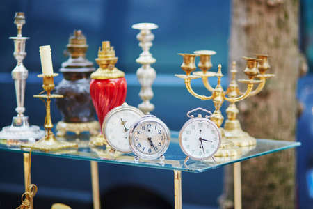 Old alarm clocks and candle holders on flea market in Paris, France