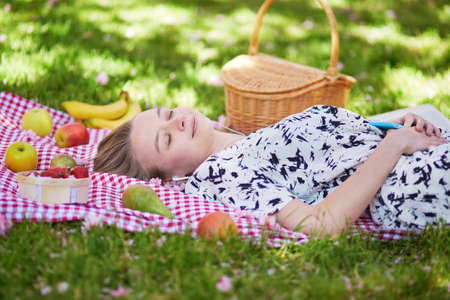 Beautiful young woman having picnic in parc, lying on her back with fruits around her