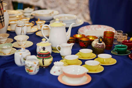 Many porcelain tea cups and pitcher on flea market in Paris, France