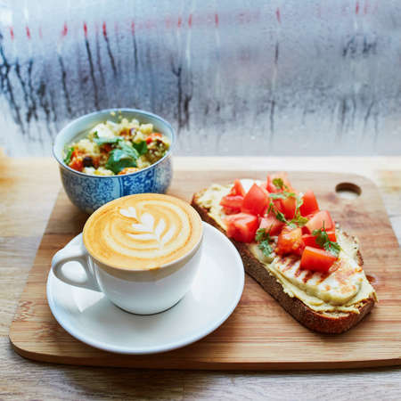 Delicious breakfast, brunch or lunch with hummus and tomato sandwich, salad and fresh hot cappuccino coffee served on cutting board near the window with water drops on wet glass at rainy day