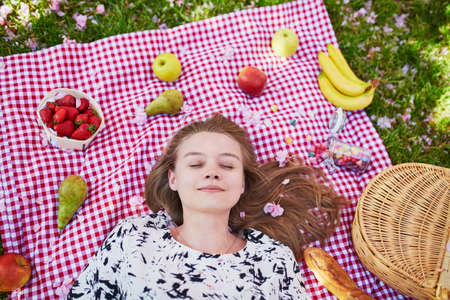 Beautiful young woman having picnic in parc, lying on her back with fruits around her, listening to the music. View from above. Relaxing or studying in park concept Stock Photo