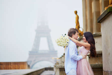 Beautiful romantic couple in love holding bunch of white roses and hugging near the Eiffel tower in Paris on a cloudy and foggy rainy day