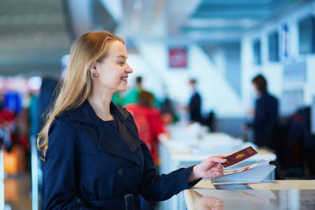 Young woman in international airport at check-in counter, giving her passport to an officer and waiting for her boarding pass