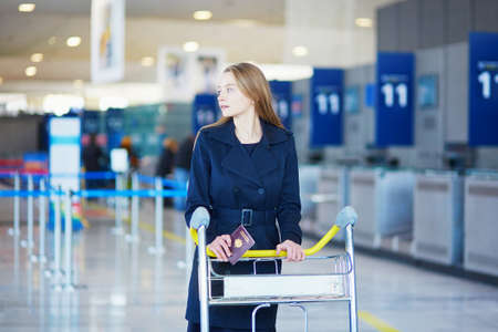 Young woman in international airport, with luggage trolley