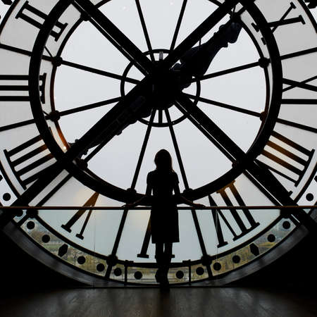 Woman silhouette standing in front of clock in the Orsay Museum, Paris, France. Unrecognizable person overlooking Paris Stock Photo