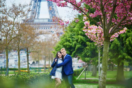 Romantic couple in Paris on a spring day near the Eiffel tower with pink cherry blossoms behind them