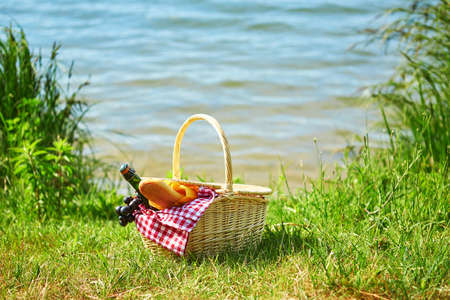 Picnic basket with food and cider bottle near the water Stock Photo