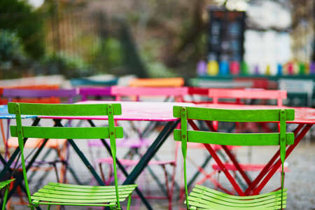 Bright colorful tables of an empty Parisian outdoor cafe on Montmartre