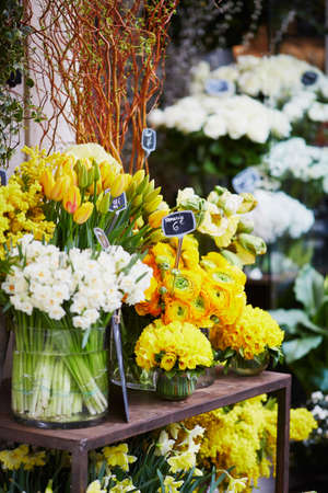 Outdoor flower market with mimosa, ranunculuses and narcissi in Paris, France