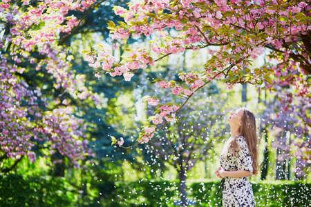 素敵な春の日の桜の季節の間に公園で晴れた日を楽しんで美しい若い女性 写真素材