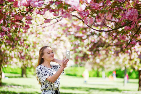 Beautiful young woman enjoying sunny spring day in park during cherry blossom season, taking photo or selfie with her mobile phone