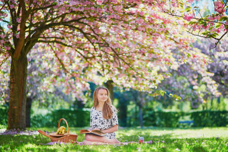 Beautiful young woman having picnic on sunny spring day in park during cherry blossom season, reading a book